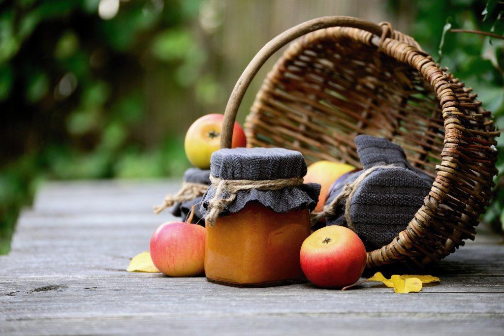 Fotobeschreibung: Nahaufnahme eines auf der Seite liegenden Weidenkorbs, vor dem ein Glas Marmelade und Äpfel liegen.