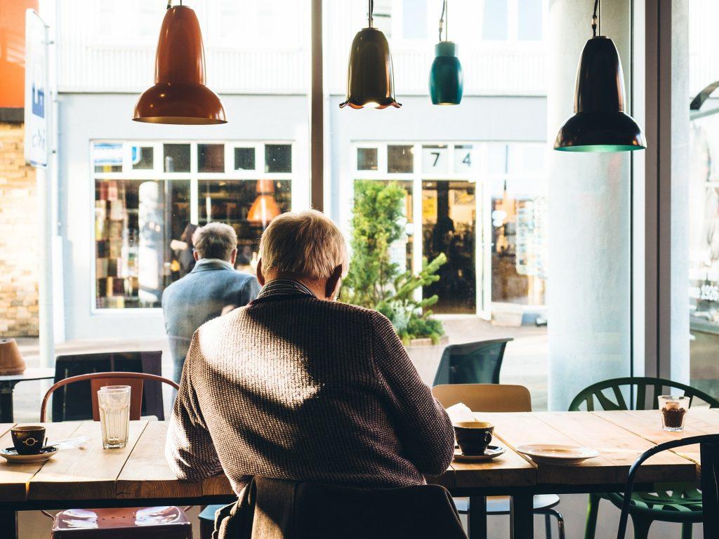 Fotobeschreibung: Nahaufnahme von hinten: Ein Mann sitzt in einem Cafe an einem Tisch. Was der Mann genau tut, sieht man nicht.