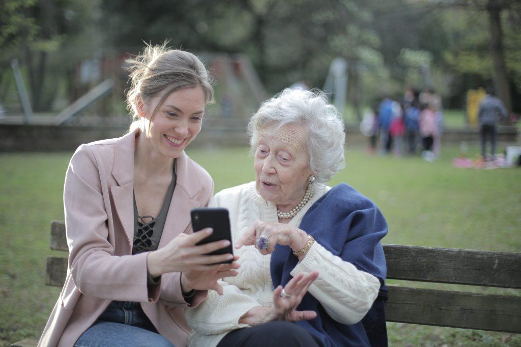 Fotobeschreibung: Eine Seniorin sitzt zusammen mit einer jungen Frau in einem Park auf einer Bank. Die junge Frau zeigt der Seniorin etwas auf dem Handy.