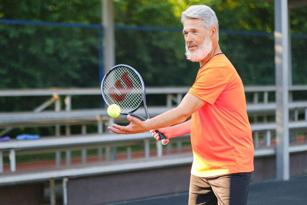 Fotobeschreibung: Senior beim Tennisspielen, kurz vor dem Aufschlag.