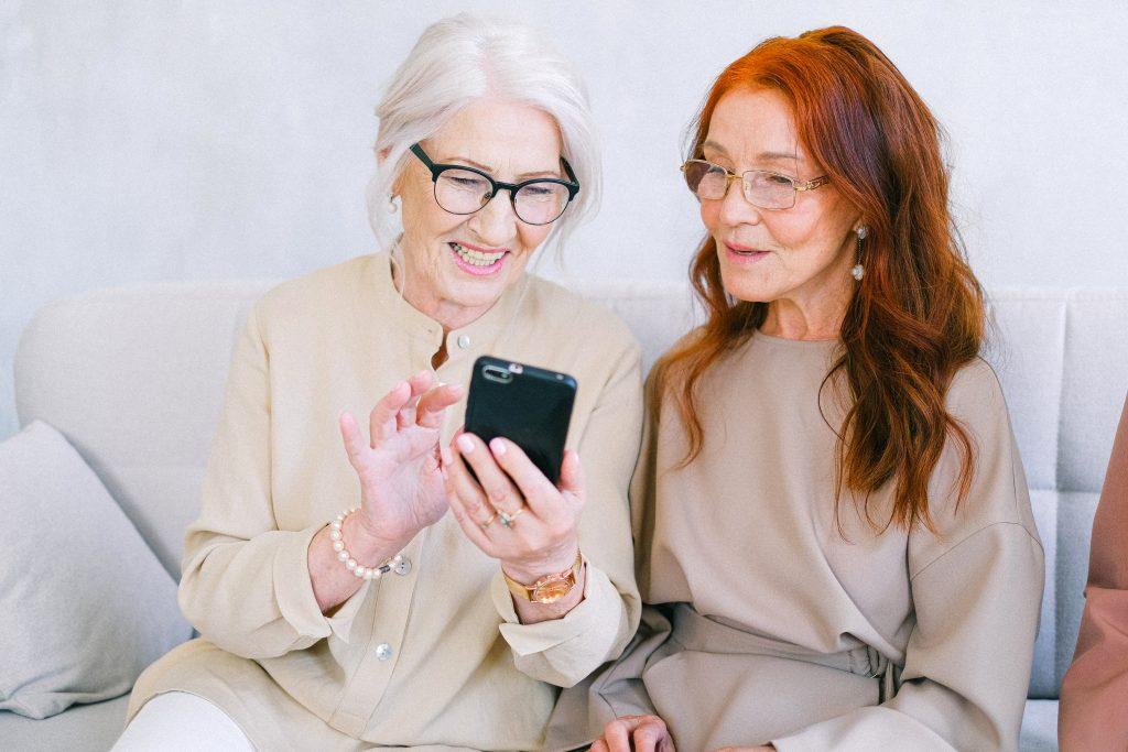 Fotobeschreibung: Zwei hübsche Seniorinnen sitzen nebeneinander und gucken zusammen auf ein Smartphone.