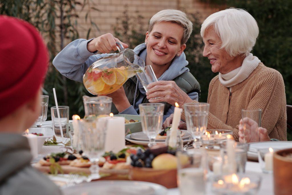 Fotobeschreibung: Nahaufnahme einer jungen Frau, die an einem Gartentisch sitzend einer Seniorin ein Glas Apfelsaft einschüttet. Der Tisch vor ihnen ist reich gedeckt.