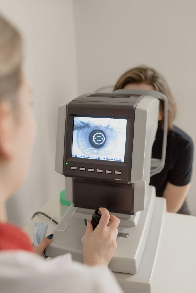 Fotobeschreibung: Nahaufnahme eines modernen Geräts zur Augenuntersuchung. Die Frau, deren Augen untersucht werden ist hinter dem Gerät kaum zu erkennen.