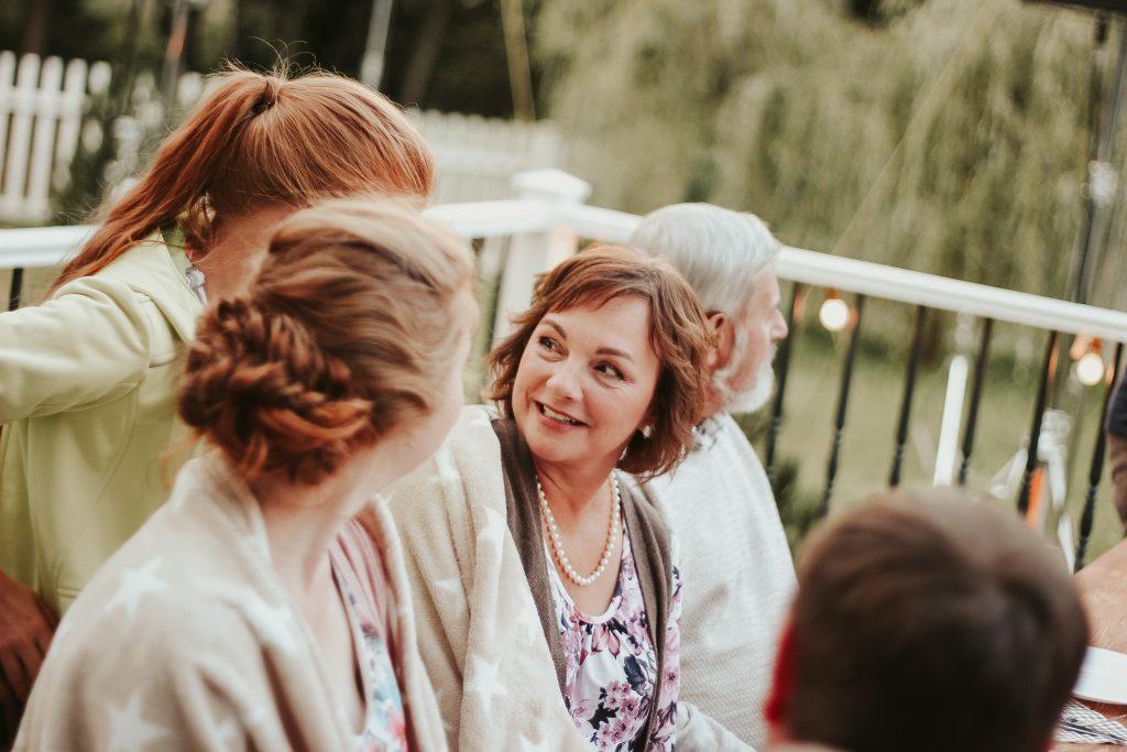 Eine fröhliche Gruppe aus Bekannten verschiedenen Alters sitzt zusammen auf einer Terasse. In der Mitte sieht man eine hübsche Frau mittleren Alters, die sich im Gespräch Richtung Kamera dreht.