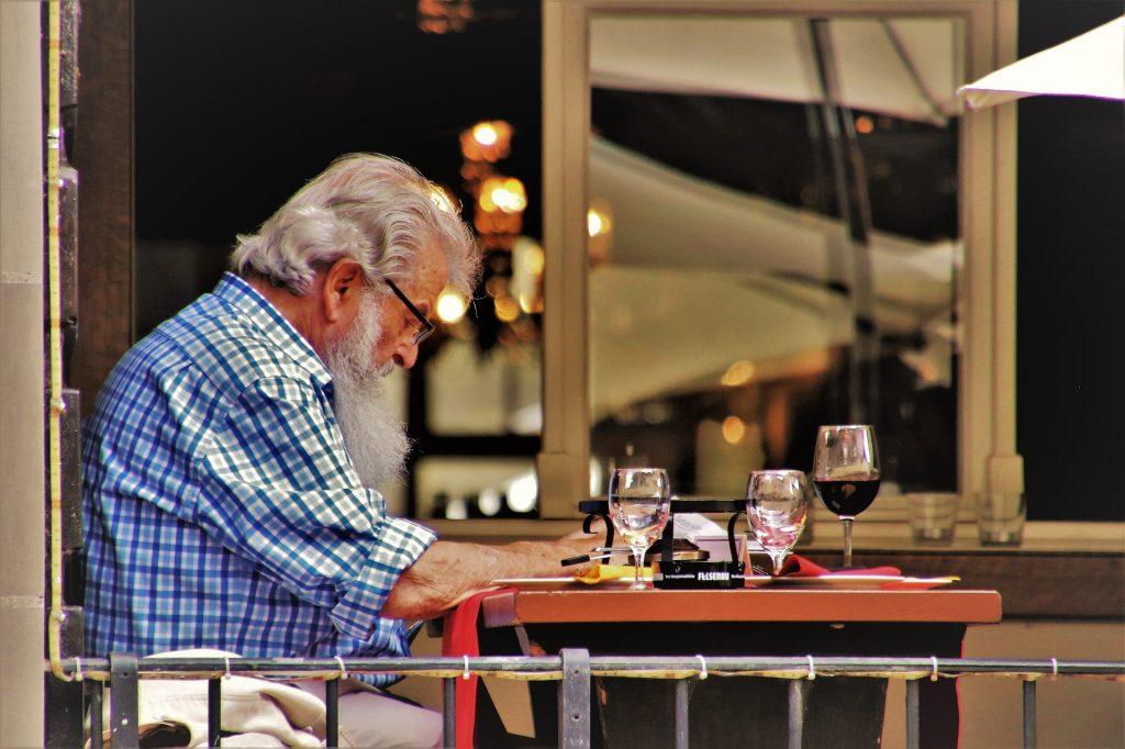 Fotobeschreibung: Ein älterer Herr im Hemd sitzt draußen in einem Cafe an einem Tisch und liest.