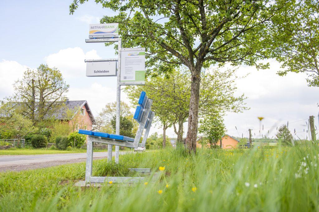 Bildtext: Zu sehen ist eine blaue Sitzbank an einer Landstraße. Neben der Bank steht ein beschilderter Pfahl, welcher es dem Reisenden durch verschiedene Schilder mit Ortsnamen ermöglicht, seinen Zielort auszuwählen. Vorbeikommende Autos wissen so, wo der Wartende hin möchte.