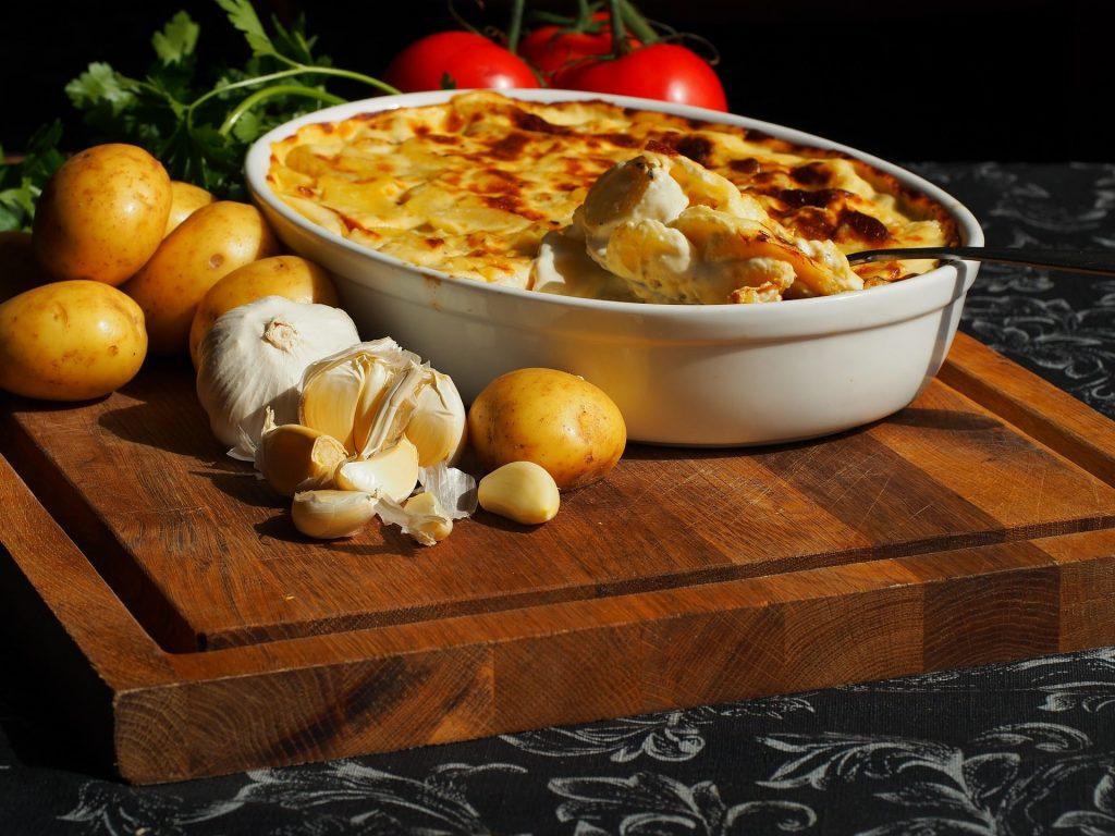 Bildtext: Nahaufnahme eines Kartoffelgerichts in einer Auflaufschale, die auf einem Holzbrett steht. Um die Form herum liegen einzelne Kartoffeln und Knoblauchzehen