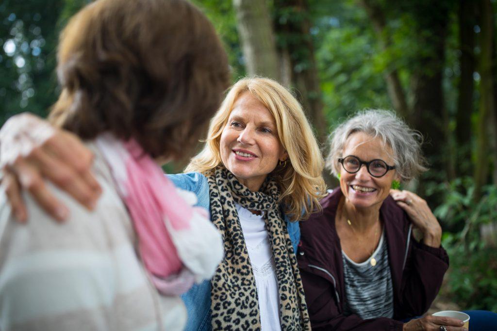 Fotobeschreibung: Drei Frauen mittleren Alters, die fröhlich nebeneinander her durch den Wald gehen.