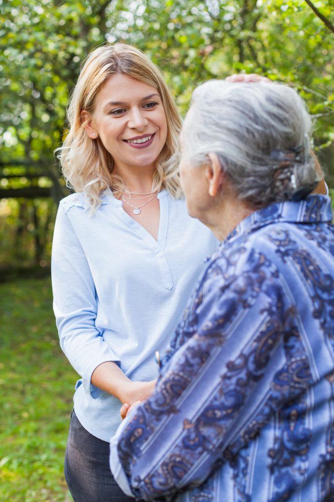 Fotobeschreibung: Nahaufnahme einer Frau mittleren Alters, die einer Seniorin während eines Spaziergangs lächelnd die Hände reicht.