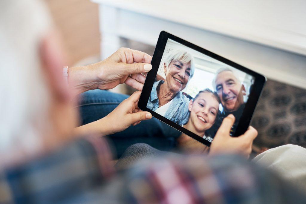 Fotobescheibung: Nahaufnahme eines Tabletts, auf dem Mann eine Familie mit kleinem Kind sieht. Gehalten wird das Tablett von einem nicht näher erkennbaren Seniorenpaar.