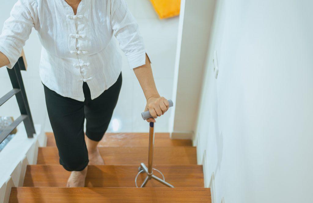 Fotobeschreibung: Nahaufnahme einer Seniorin, die mit Hilfe einer Gehstockhilfe eine Treppe in einem Wohnhaus empor steigt.