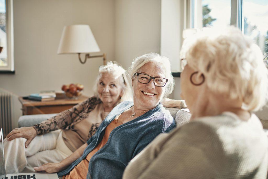 Fotobeschreibung: Drei fröhliche Seniorinnen sitzen zusammen auf einem Sofa in einer Wohnung und unterhalten sich.