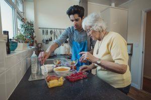 Fotobeschreibung: Ein junger Mann steht neben einer Seniorin in einer Küche und hilft ihr beim Kochen.