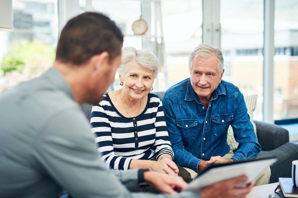 Fotobeschreibung: Ein Senioren-Pärchen sitzt mit einem jüngerem Mann zusammen. Der jüngere Mann erklärt ihnen etwas und sie hören lächeln zu.