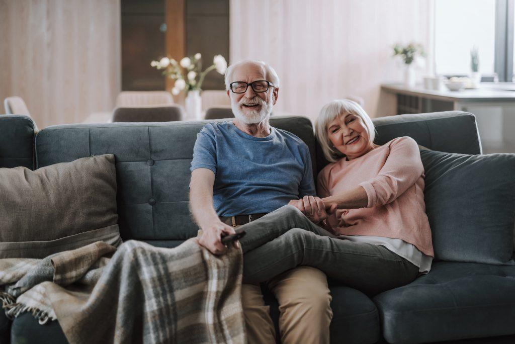 Fotobeschreibung: Ein Pärchen im fortgeschittenen Alter sitzt zusammen auf einem Sofa im Wohnzimmer. Die Frau hat ihre Beine hierbei über die Beine des Mannes geschlagen.