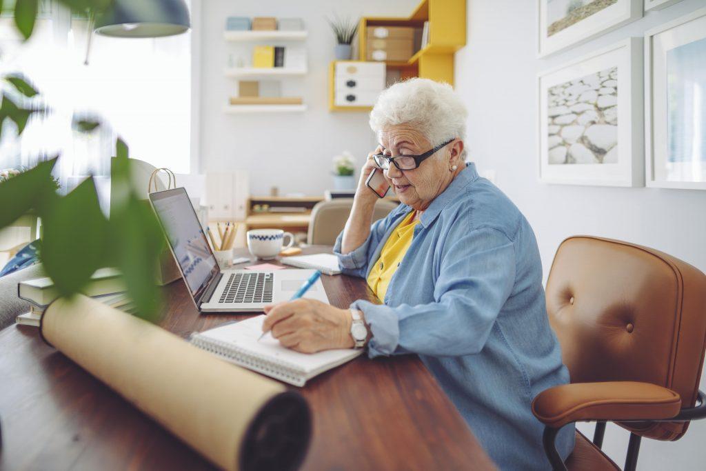 Fotobeschreibung: Eine ältere Dame sitzt telefonierend am Schreibtisch und macht sich Notizen.