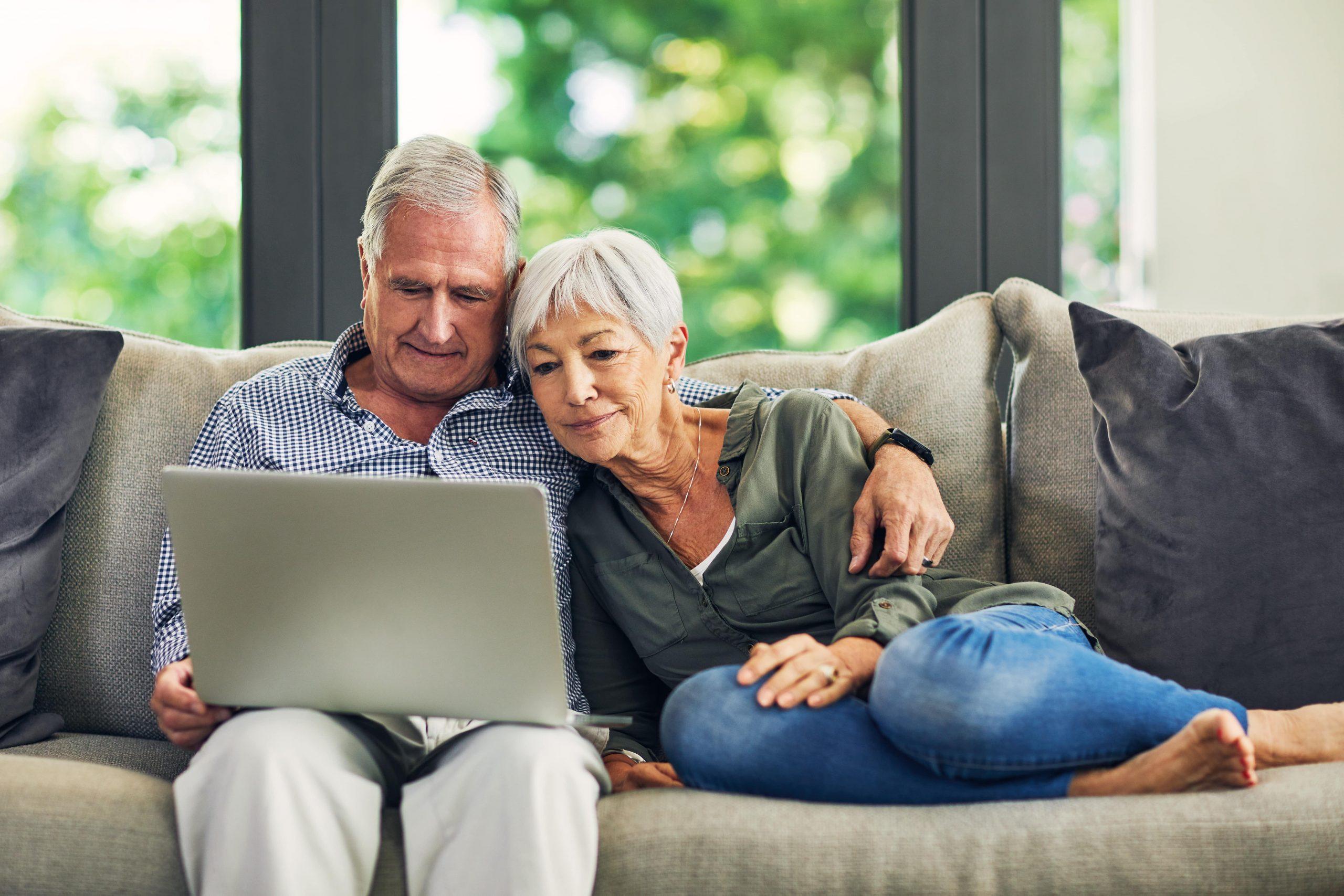 Fotobeschreibung: Ein Seniorenpärchen sitzt zusammen auf dem Sofa. Der Mann hat einen Laptop auf dem Schoß, auf dem beide etwas lesen. Die Frau hat die Beine angezogen und lehnt an der Seite ihres Mannes.