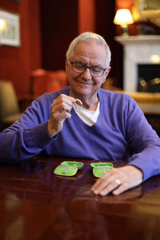 Fotobeschreibung: Ein älterer Herr sitzt in einem Wohnzimmer an einem Tisch. Er guckt sich ein Hörsystem an und lächelt.