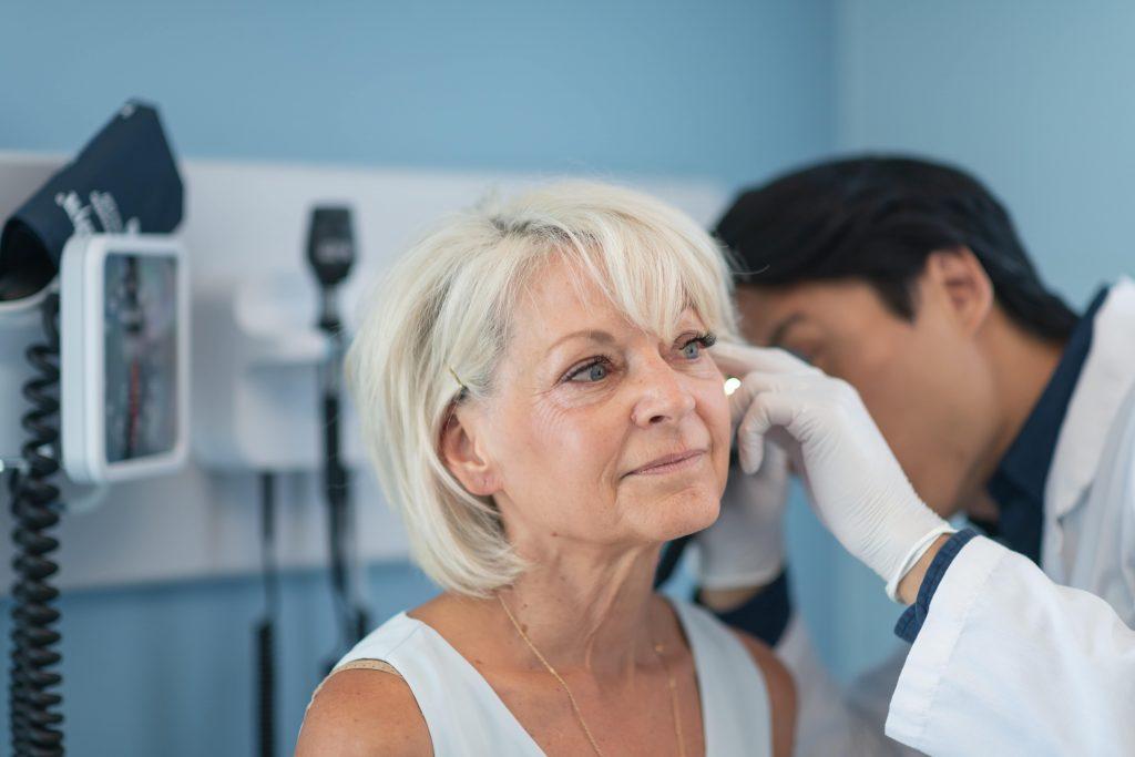 Fotobeschreibung: Ein Ohrenarzt untersucht das Ohr einer Seniorin.