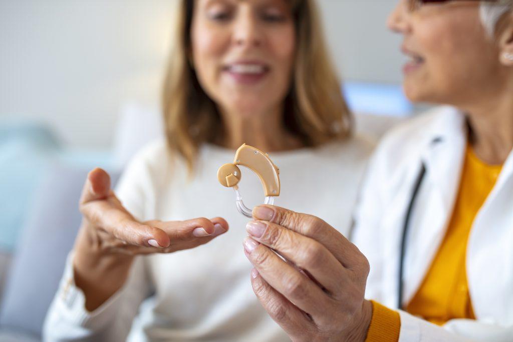 Nahaufnahme einer Hörgerateakustikerin, die einer Seniorin ein Hörgerät zeigt.