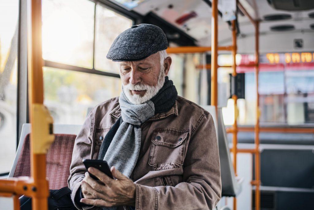Fotobeschreibung: Nahaufnahme eines Senioren, der in Mantel und mit einem Hut gekleidet in einem Bus sitzt und auf sein Handy schaut.