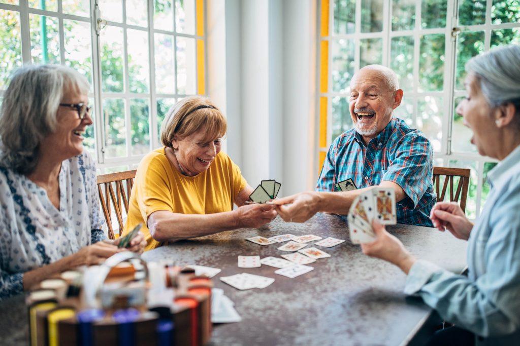 Fotobeschreibung: Zwei Senioren und zwei Seniorinnen sitzen lachend zusammen an einem Tisch in einem Wohnzimmer und spielen Karten.