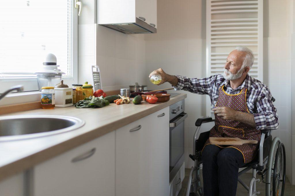 Fotobeschreibung: Ein Senior sitzt in einem Rollstuhl in seiner Küche und bereitet eine Mahlzeit zu. Die Zutaten befinden sich auf der Arbeitsplatte.