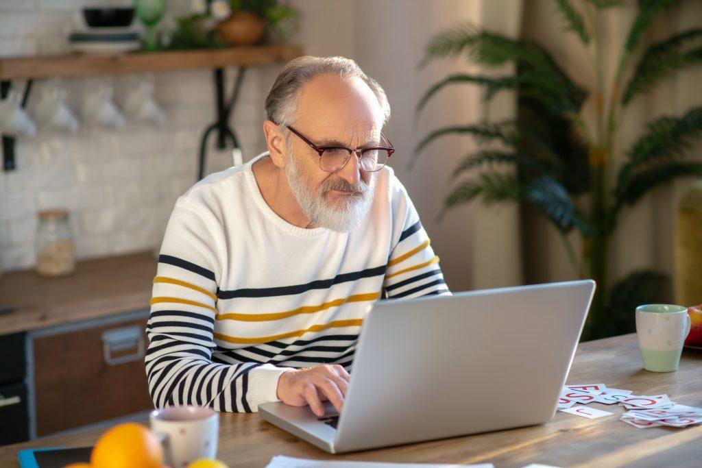 Fotobeschreibung: Nahaufnahme von einerem Senioren, der mit seinem Laptop am Tisch sitzt.