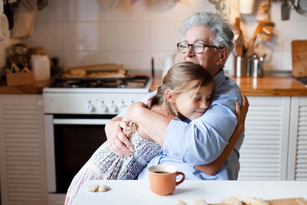 Fotobeschreibung: Nahaufnahme einer Großmutter, die ihre Enkelin in der Küche umarmt.