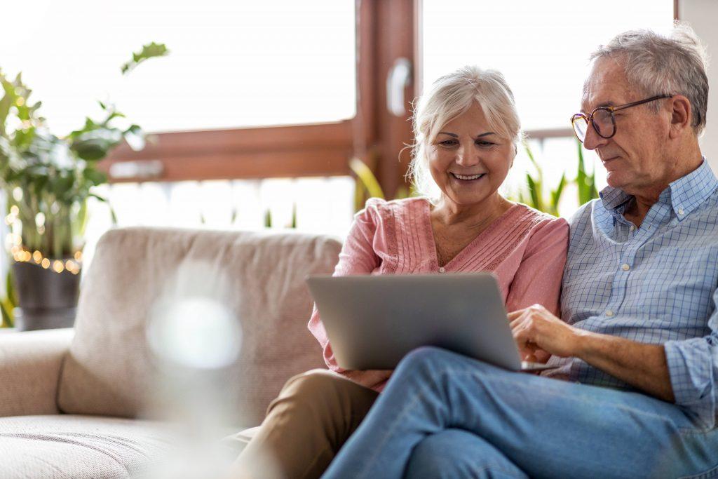 Fotobeschreibung: Ein Seniorenpärchen, dass zusammen auf einem Sofa im Wohnzimmer sitzt und zusammen auf einen Laptop guckt.