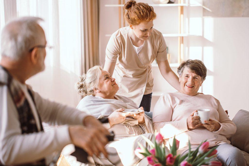 Fotobeschreibung: Eine kleine Gruppe aus einem Senior und zwei Seniorinnen sitzt zusammen, während sich eine Haushaltshilfe oder Pflegerin mit ihnen unterhält.
