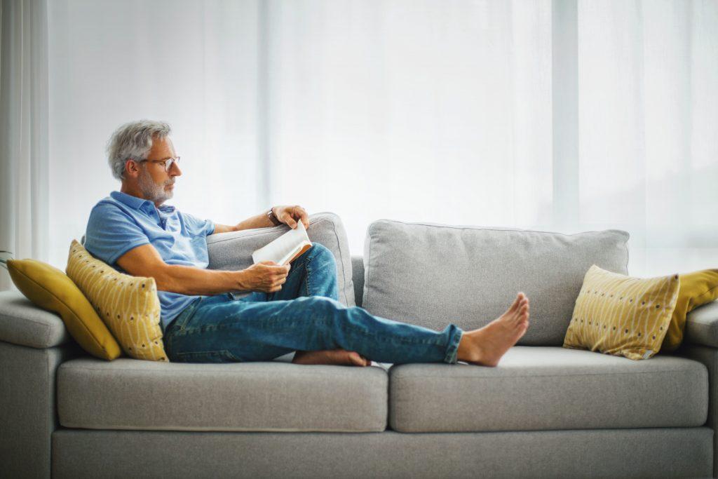 Fotobeschreibung: Ein Mann mittleren Alters sitzt längs mit ausgestrecktem Bein auf einem modernen grauen Sofa und liest ein Buch.