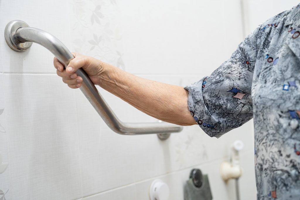 Fotobeschreibung: Nahaufnahme einer Seniorin, die sich an einem Haltegriff im Badezimmer festhält.