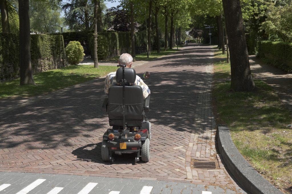 Fotobeschreibung: Rückansicht eines Senioren, der auf einem elektronischen Rollstuhl eine gepflasterte und von Bäumen gesäumte Straße entlang fährt.