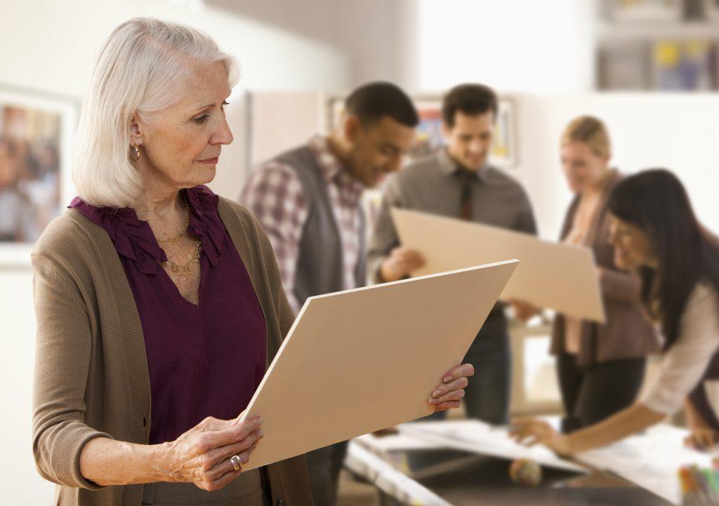 Nahaufnahme einer gut gekleideten Seniorin, die sich während einer Ausstellung ein Bild in ihren Händen anschaut. Im Hintergrund stehen vier weitere Personen, die sich Bilder ansehen.