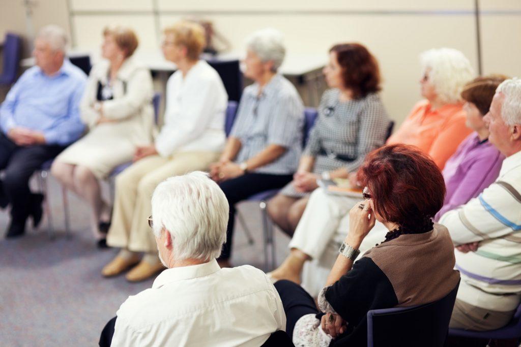 Fotobeschreibung: Eine große Gruppe Senioren und Seniorinnen sitzen im Zuge eines Seminars im Halbkreis.