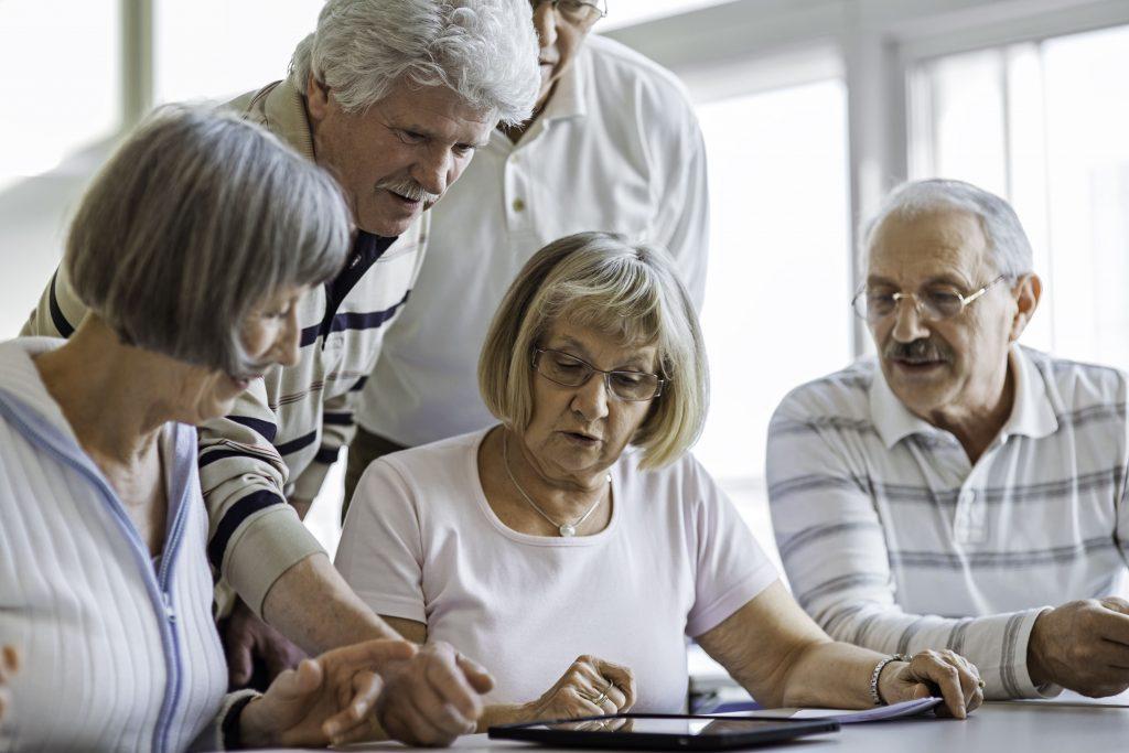 Fotobeschreibung: Nahaufnahme einer Seniorngruppe, die sich während eines Seminars über ein Tablett beugen, dass auf dem Tisch liegt.