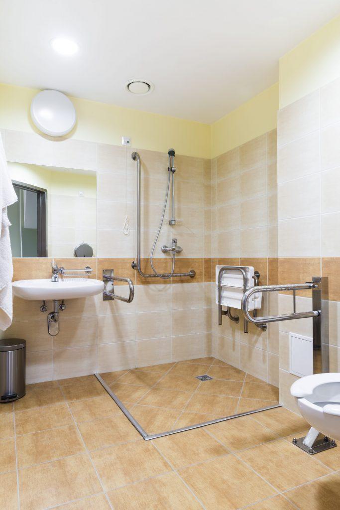 Fotobeschreibung: Nahaufnahme einer ebenerdigen Dusche in einem barrierefreien Badezimmer.