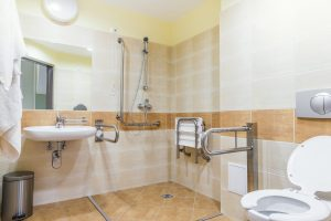Fotobeschreibung: Ein barrierefreies Badezimmer mit begehbarerer Dusch inklusive Duschhocker und zusätzlichen Griffen am Waschbecken und der Toilette.