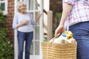 Fotobeschreibung: Ein Helfer bringt einer Seniorin, die nur unscharf zu sehen ist, Einkäufe nach Hause.