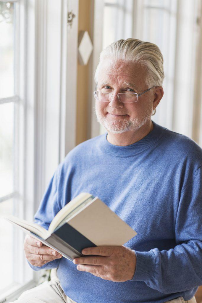 Fotobeschreibung: Nahaufnahme eines freundlich in die Kamera lächelnden Senioren mit blauem Pullover, der ein aufgeschlagenes Buch in den Händen hält.