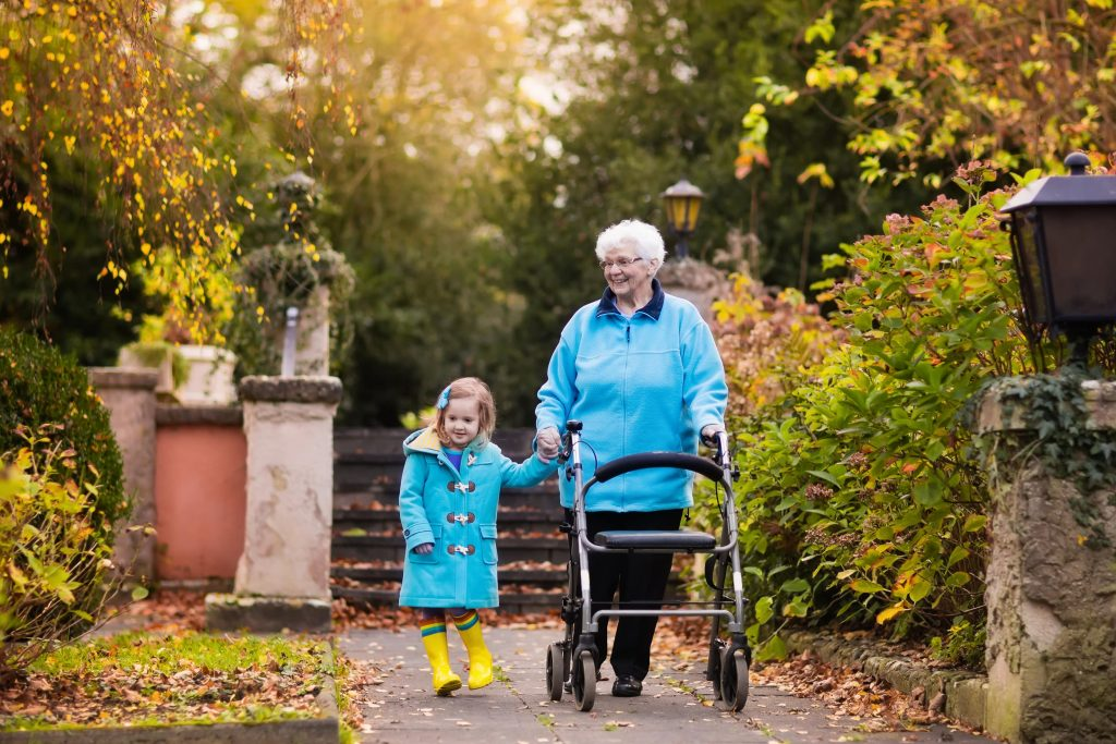 Fotobeschreibung: Totalaufnahme einer Seniorin mit Rollator, die zusammen mit ihrer Enkelin durch einen Park läuft. Es ist Herbst und beide tragen eine hellblaue Jacke.
