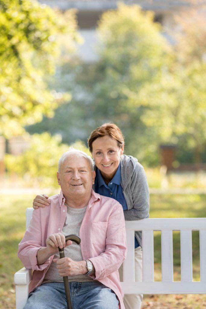 Fotobeschreibung: Ein älterer Herr sitzt auf einer weißen Holzbank in einem Park. Hinter ihm steht eine Pflegerin. Beide lächeln in die Kamera.