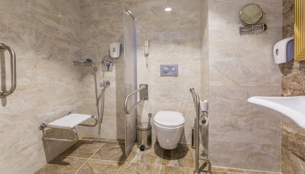 Fotobeschreibung: Ein barrierefreies Badezimmer mit begehbarer Dusche inklusive Duschhocker und zusätzlichen Haltegriffen an der Toilette