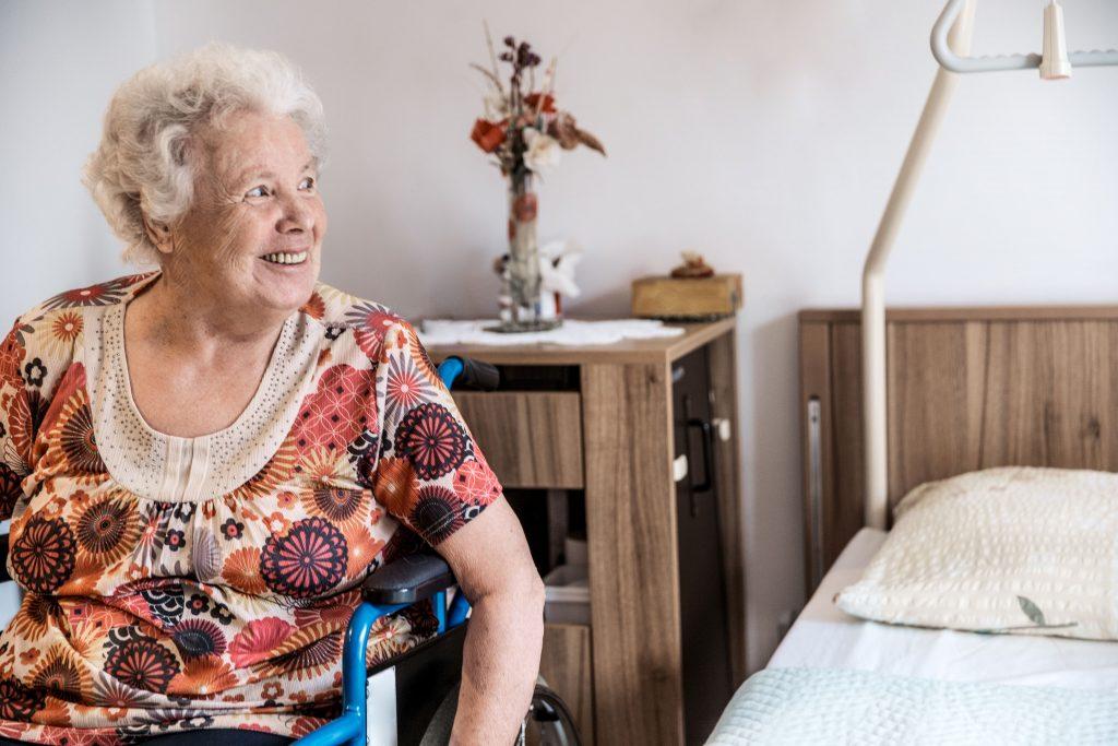 Fotobeschreibung: Eine Frau, die im Rollstuhl in ihrem Schlafzimmer sitzt und zur Seite schaut. Im Hintergrund sieht man am Bett eine Aufstehhilfe.