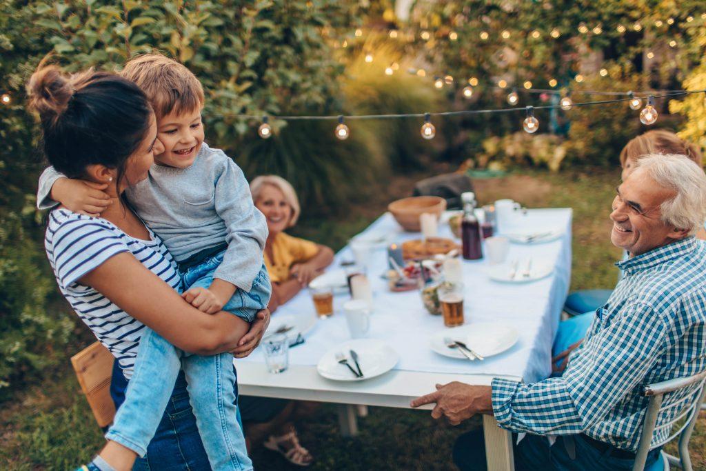 Fotobeschreibung: Eine aus drei Generationen bestehende Familie sitzt an einem großen gedeckten Gartentisch. Im Vordergrund steht eine junge Frau mit einem kleinen Jungen auf dem Arm.