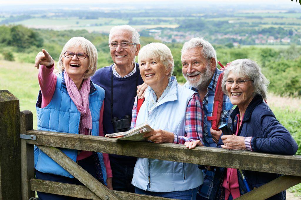 Fotobeschreibung: Eine Gruppe aus wandernden Senioren und Seniorinnen steht zusammen an einem Holzzaun in der Natur. Alle betrachten fröhlich etwas, dass außerhalb des Sichtfelds.