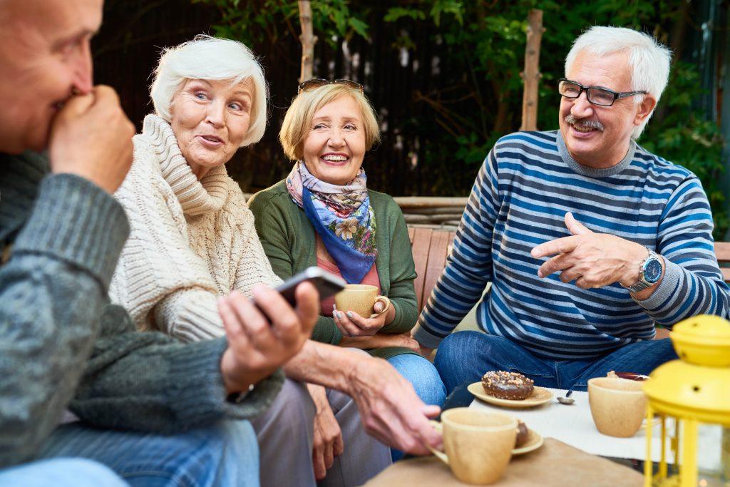 Fotobeschreibung: Zwei Männer und zwei Frauen mittleren Alters sitzen zusammen im Garten, unterhalten sich und trinken Kaffee.
