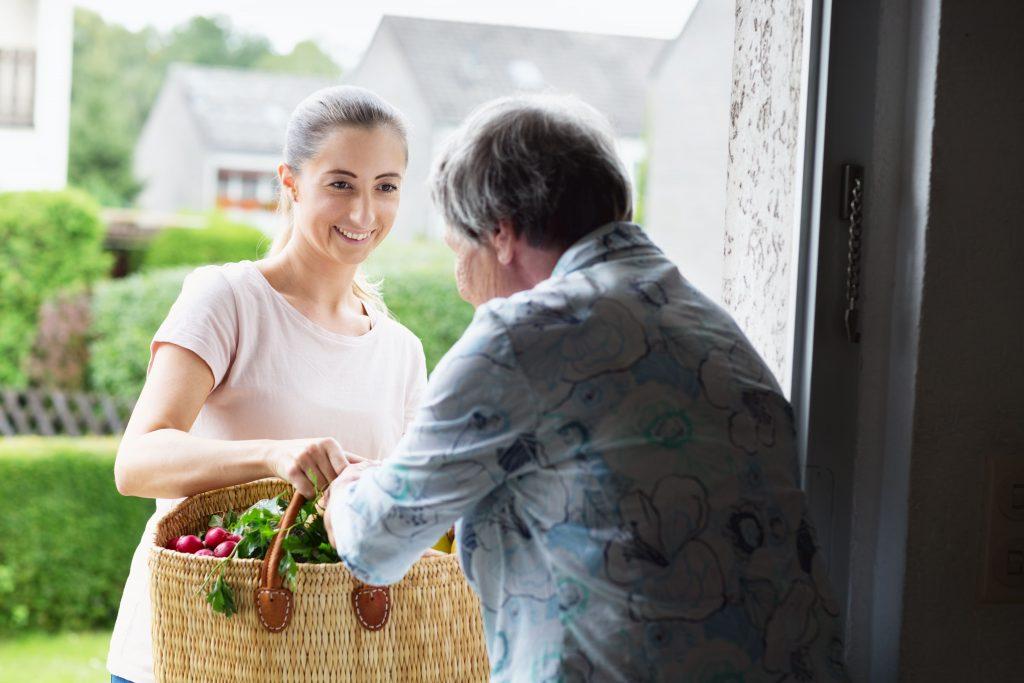 Fotobeschreibung: Eine junge, lächelnde Frau bringt einer Seniorin Einkäufe an die Tür.