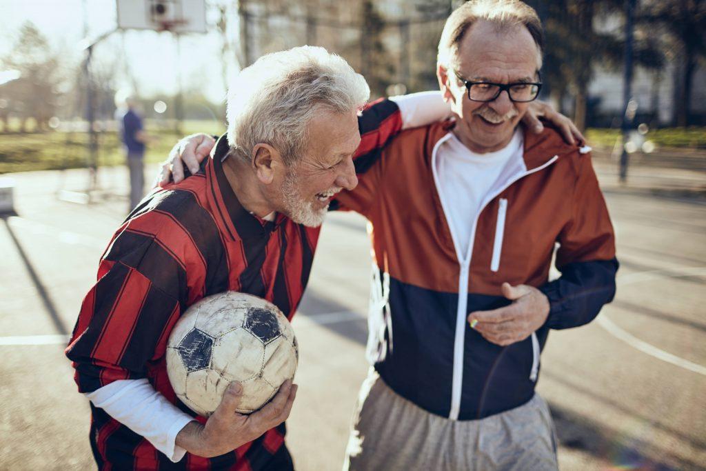 Fotobeschreibung: Zwei Männer im Seniorenalter nach dem Sport. Sie haben freundschaftlich jeweils einen Arm um die Schulter des anderen gelegt. Einer von Ihnen hält einen Fußball.